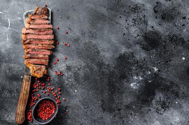 Steak de surlonge grillé sur un couperet. le milieu de cuisson. fond noir
