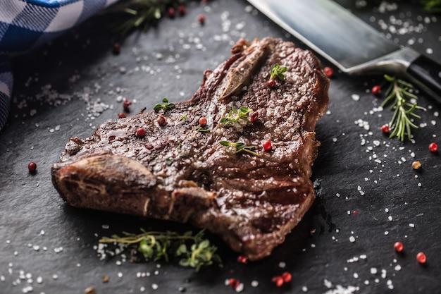 Steak t-bone de boeuf avec sel poivre et romarin sur plaque d'ardoise.