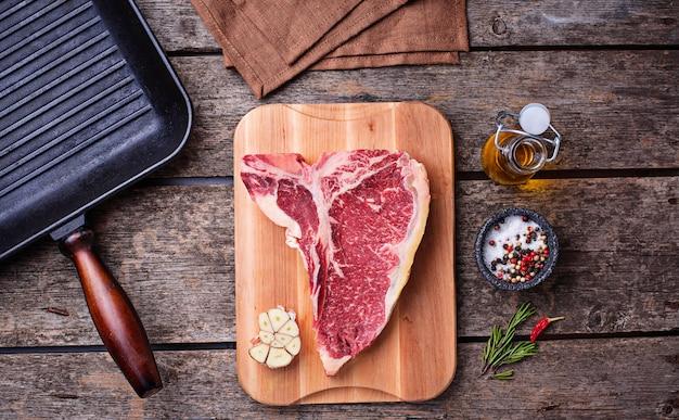 Steak t-bone cru et gril en fer