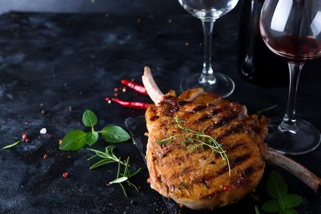 Steak de t-bone grillé avec un verre et une bouteille de vin sur une table en pierre.