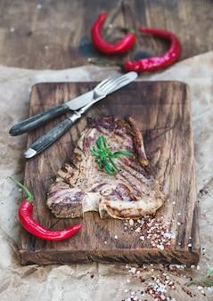 Steak de t-bone de viande cuite sur une planche de service avec des piments rouges, des épices, du romarin frais sur du papier kraft huileux et une surface en bois rustique
