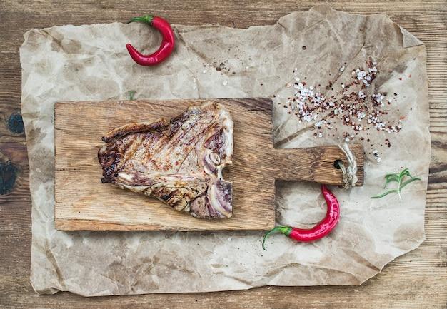 Steak t-bone de viande cuite sur plateau de service avec piments rouges