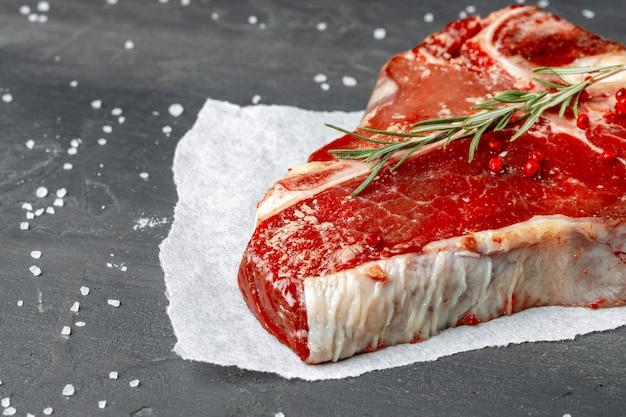 Steak t-bone de viande fraîche crue avec des épices sur un fond sombre, close up