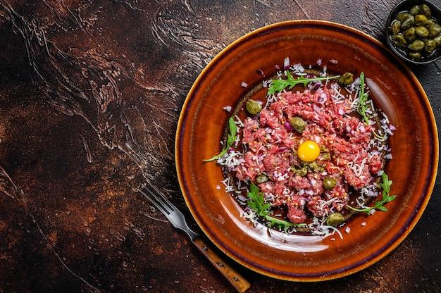 Steak tartare de bœuf au jaune d'œuf cru, câpres marinées et parmesan. fond sombre. vue de dessus. espace de copie.