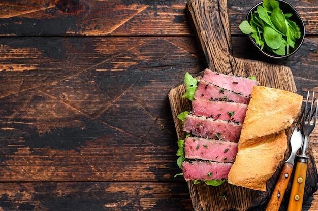 Steak de thon ahi grillé et sandwich à l'avocat avec roquette sur une planche à découper