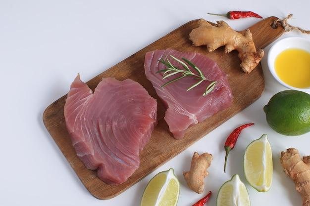 Steak de thon cru planche à découper en bois tranche de citron vert huile d'olive romarin gingembre frais racine de piment chili fond blanc espace copie
