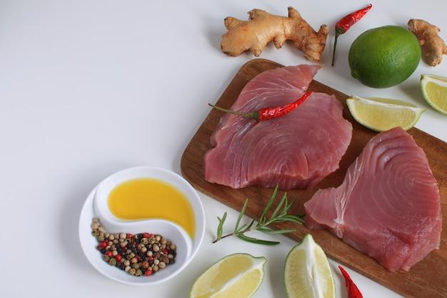 Steak de thon cru planche à découper en bois tranche de citron vert huile d'olive romarin racine de gingembre frais piment rouge