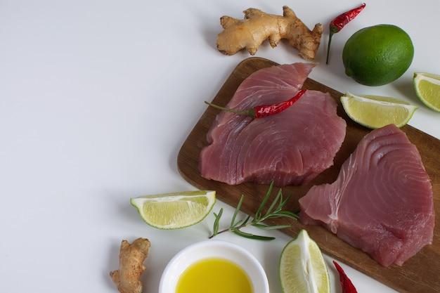 Steak de thon cru planche à découper en bois tranche de citron vert huile d'olive romarin racine de gingembre frais