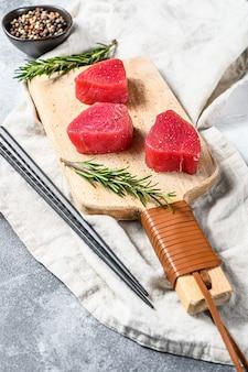 Steak de thon frais sur une planche à découper. fond gris. vue de dessus