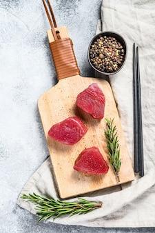 Steak de thon frais sur une planche à découper. mur gris. vue de dessus