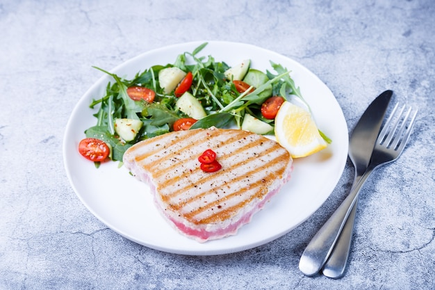 Steak de thon grillé avec légumes frais, roquette, épinards et citron. fermer.