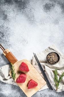Steak de thon rouge cru. fond gris. vue de dessus. espace pour le texte