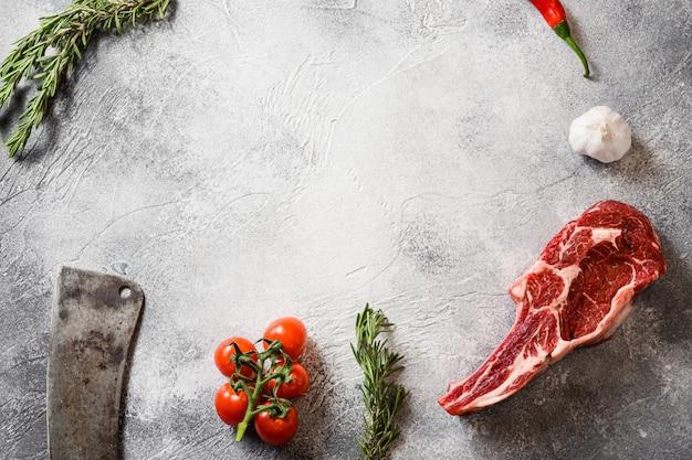 Steak de tomahawk angus noir cru ou steak de spencer coupé avec le couteau de couperet américain à viande