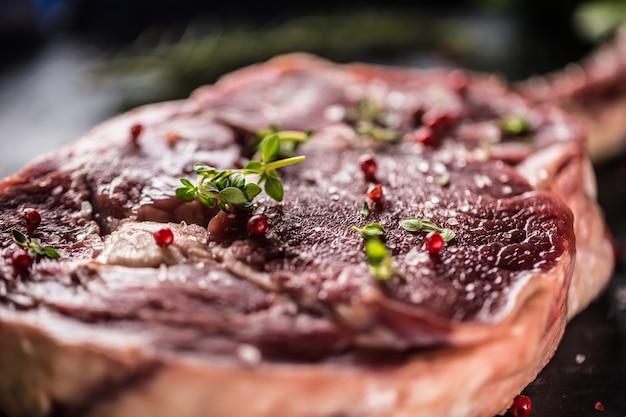 Steak de tomahawk de boeuf cru avec sel, poivre et romarin sur plaque d'ardoise.