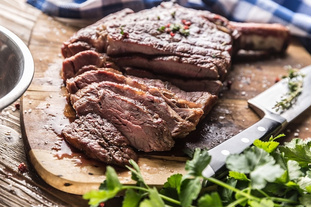 Steak de tomahawk fraîchement grillé sur plaque d'ardoise avec sel poivre romarin et herbes de persil. morceaux tranchés de steak de boeuf juteux.
