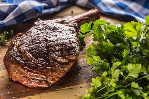 Steak de tomahawk fraîchement grillé sur plaque d'ardoise avec sel poivre romarin et herbes de persil.