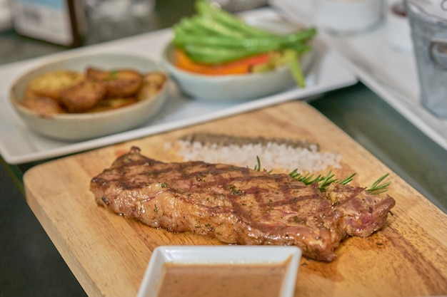 Steak avec trempette, poivre, sel et feuille de thym sur plaque de bois