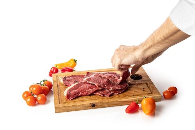 Steak de veau cru sur une planche à découper en bois avec une main le ramassant sur fond blanc