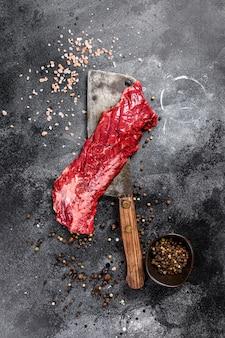 Steak de vegas en bande crue sur un couperet à viande.