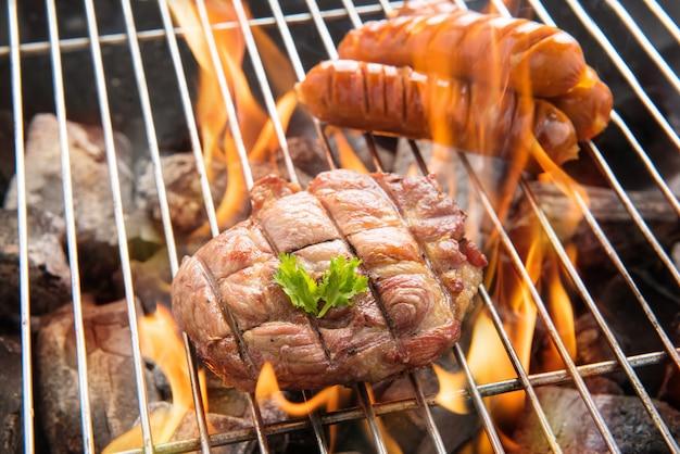 Steak de viande barbecue et saucisses sur le grill