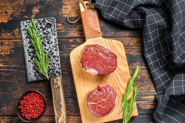 Steak de viande de boeuf cru filet de filet sur une planche à découper. surface en bois foncé. vue de dessus.