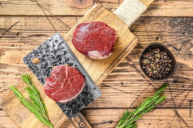 Steak de viande de boeuf cru filet de filet. surface en bois. vue de dessus.