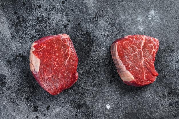 Steak de viande de boeuf cru filet de filet. surface noire. vue de dessus.