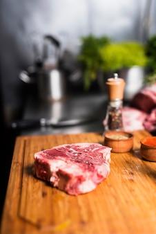 Steak de viande crue avec des épices à bord