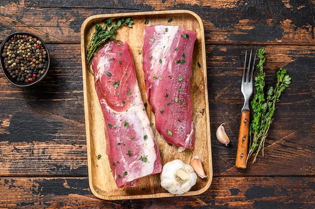 Steak de viande de filet de porc mariné au thym. fond en bois foncé. vue de dessus.