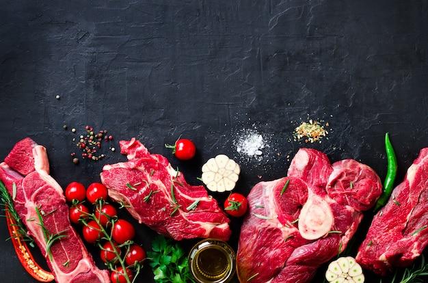 Steak de viande fraîche crue avec tomates cerises, piment, ail, huile et herbes