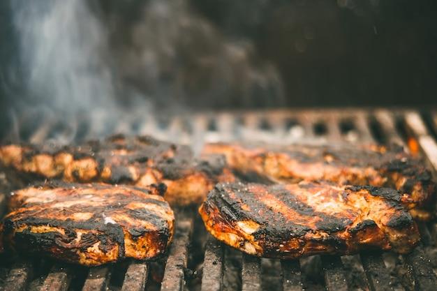 Steak de viande frit sur une grille avec de la fumée et du feu