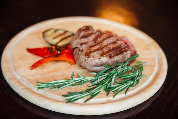 Steak de viande sur une plaque de bois avec un plat de légumes grillés.