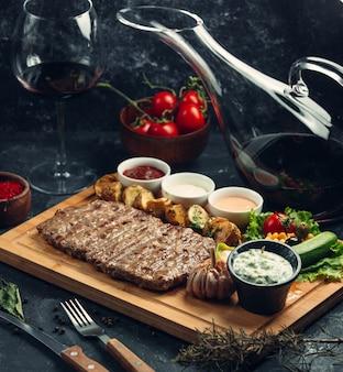 Steak de viande avec sauce dip et vinaigrettes sur une planche de bois.