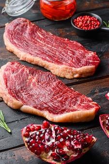 Steaks de boeuf bio cru picanha avec assaisonnement, romarin, tpmators, huile de piment épicé et grenades sur fond de bois sombre ancien, mise au point sélective de vue latérale.