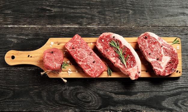Steaks de bœuf black angus cru frais sur planche de bois: filet, coupe denver, contre-filet, faux-filet