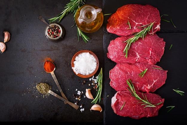 Steaks de boeuf cru avec des épices et du romarin.