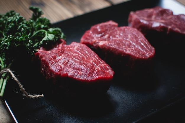 Steaks de boeuf cru sur une plaque noire