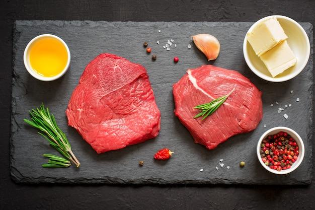 Steaks de boeuf cru et romarin sur une ardoise noire. vue de dessus.