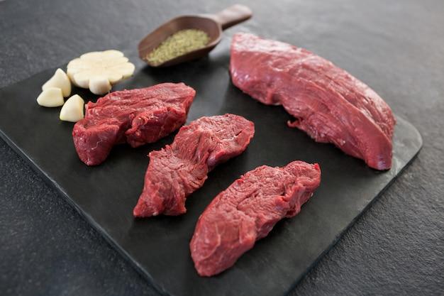Steaks de boeuf, épices et ail sur plaque d'ardoise