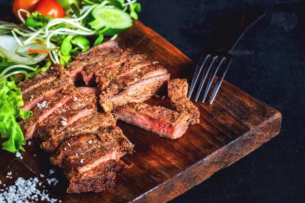 Steaks de bœuf grillé et salades santé sur la table