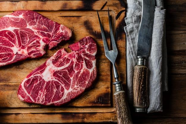Steaks de boeuf marbrés crus sur une planche à découper en bois