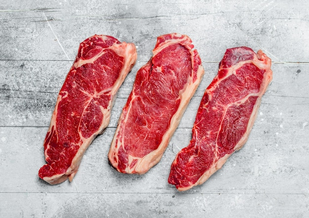 Steaks de bœuf marbrés crus. sur une surface rustique.