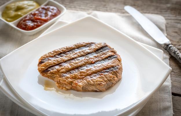 Steaks de boeuf sur la plaque carrée blanche
