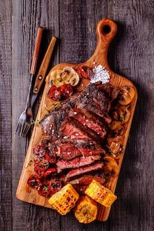Steaks de boeuf avec tomates grillées, champignons et maïs.