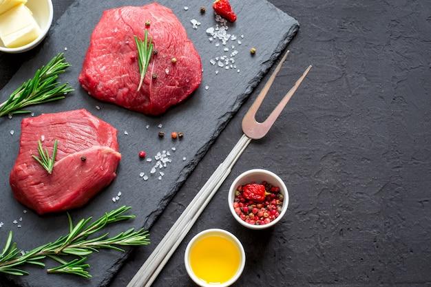 Steaks de boeuf à la viande crue sur ardoise noire, épices et ingrédients pour la cuisson. vue de dessus avec espace de copie