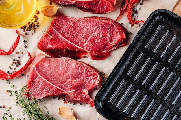 Steaks de boeuf à la viande prêts à être cuisinés avec de l'huile d'olive et des épices