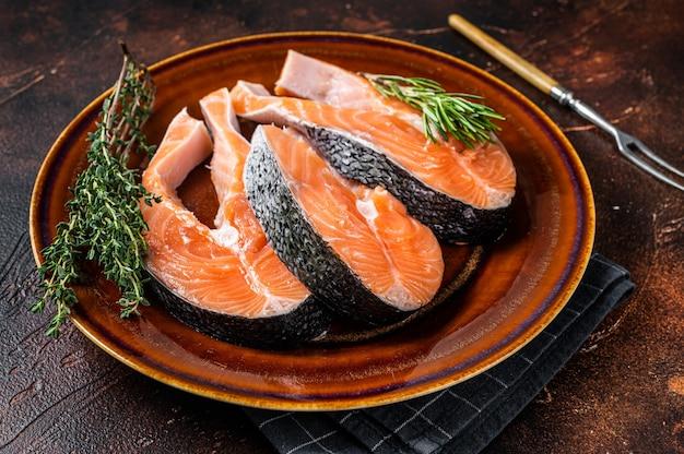 Steaks crus de saumon sur assiette rustique aux herbes. fond sombre. vue de dessus.