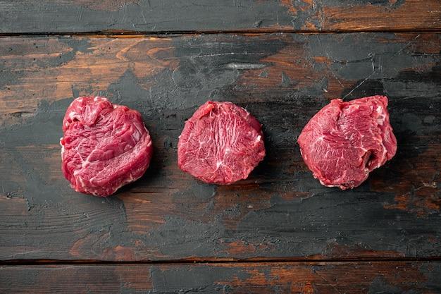 Steaks de filet de boeuf cru avec des épices, sur la vieille table en bois sombre