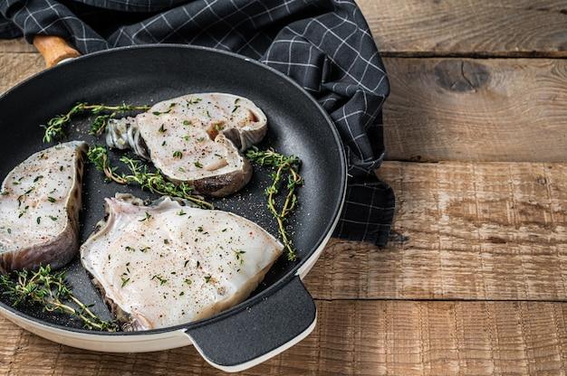 Steaks de filet de loup de mer crus frais dans une poêle avec des herbes. fond en bois. vue de dessus. espace de copie.