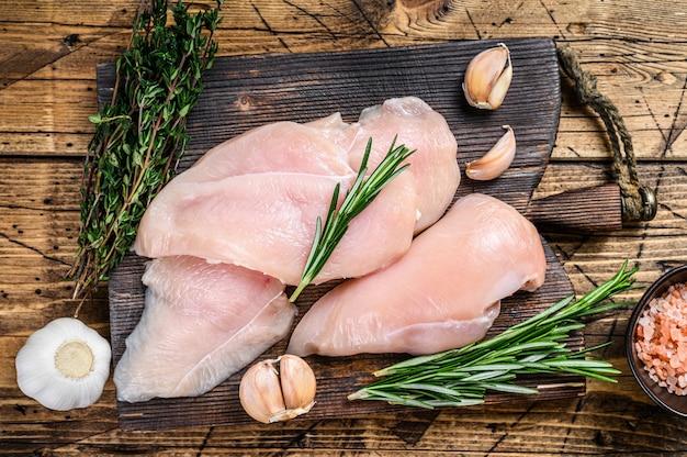 Steaks de filet de poitrine de poulet coupés en tranches et crus frais sur une planche à découper en bois avec un couteau de cuisine. fond en bois. vue de dessus.